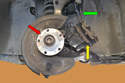 With the rotor removed and the caliper hanging safely (green arrow), clean the mounting flange (red arrow) and remove the old pads (yellow arrow).