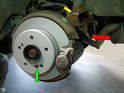 This photo shows the new rotor or disc installed with the locator screw on (green arrow), and the new caliper and pads attached.