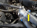 Remove the clamp and large hose coming out of the thermostat housing (yellow arrow).