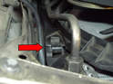 Remove the clip holding the shroud base to the radiator (red arrow) on the passenger side.