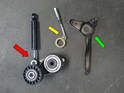 Here is a photo for the tensioner and shock (red arrow), the adjusting rod (yellow arrow) and tensioner bracket (green arrow).