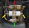 With the cover removed you can see the fuel pump (red arrow) the fuel accumulator (green arrow) and the fuel filter, including the two fittings (yellow arrow).