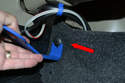 Open the trunk and remove the eight plastic clips (four on each side) holding the carpet in place.