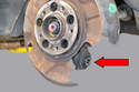 Spin the dust shield until you have access to the wheel carrier bushing.