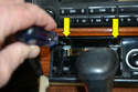 Remove the ashtray from the assembly and, using a Phillips-head screwdriver, remove the two screws (yellow arrows) holding the assembly to the console.