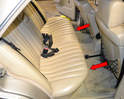 Locate the two metal clips under the center of the passenger and driver side rear seats (red arrows).