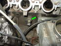 Shown here is the front knock sensor (green arrow) with the harness already removed.