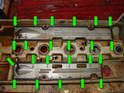 Now turn the valve cover over and remove the small Phillips head screws that hold the baffle plates to the inside of the valve covers (green arrows).