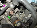 Remove the two long 10mm nuts and bolts that hold the power steering fluid reservoir to the engine and set it aside as shown here.