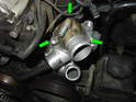 Fit the thermostat cover on the top of the water pump and re-install the three 10mm bolts (green arrows).