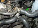 Install the upper radiator hose going from the top water pump fitting to the radiator (green arrow).