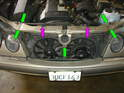 Now install the upper radiator support panel and install the five 10mm bolts holding it in place (green arrows) as well as the two large spring clips holding the radiator to the panel (purple arrows).