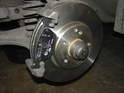 Fit the outer brake pad on the caliper frame as shown here.