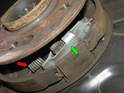 Looking up at the bottom of the parking brake, You'll see the two parking brake shoes held in place by the lower retaining spring (red arrow) and the expanding frame that spreads the pads out when you engage the parking brake (green arrow).
