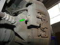 Loosen and remove the 5mm hex bolt that secures the brake wear sensor fixture to the caliper (green arrow).