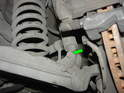 Shown here is the 17mm bolt that secures the shock to the control arm (green arrow).