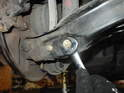 Remove the 17mm nut while counter-holding the 17mm bolt head on the other side of the control arm.