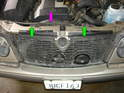 Remove the two spring clips that hold the fan shroud in place on the top of the radiator support (green arrows).