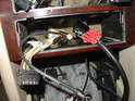 Now re-fit the front center console panel and route the new wiring harness so it passes through the hole for the stereo.