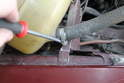 Unscrew hose clamp below the tank using a flat head screw driver.