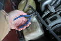 Clip the cable tie from the hose to free the tank.