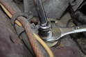 Hold the bottom 17mm nut with an open end wrench while you loosen and remove the top nut with a 17mm socket as shown here.