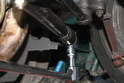 Using a 17mm socket, loosen and remove the bolt holding the steering dampener strut.