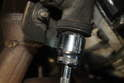 Using a 23mm, loosen and remove the bottom bolt loosening the idler arm.