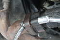 Use a 12mm and 13mm wrench and socket to loosen and remove the exhaust line on the other side.