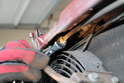 With a 10mm open end wrench, loosen and remove the cable from the hood latch.