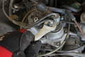 Using a 12mm open-end wrench, loosen and remove the fuel line from the warm-up compensator.