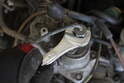 Using a 14mm open-end wrench, loosen and remove the fuel line from the other side of the warm up regulator.