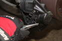 With the needle nose pliers, remove the brake pad retaining spring.