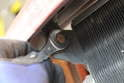 The bolts at the top of the AC condenser only have to be loosened allowing the AC condenser to swing back.