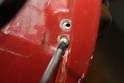 In order to remove the door handle, you will first have to remove two Phillips head screws that hold the handle.