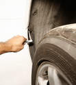Remove the fastener in the wheel well arch on each side.