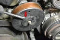 Use a flathead screwdriver and remove the cap on the tensioner pulley (red arrow).