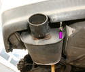 The OEM muffler also has a grounding flange (arrow).
