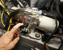 Listen and feel the hydraulic pump's relay (arrow) for a click when the top's switch is pulled.