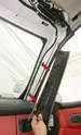 Sliding the covers up the A-pillars frees them from the slots in the windshield frame (arrows).