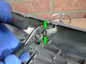 Securely grab the locking clip with your pliers at the location indicated by the green arrows.