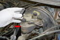 While you are pushing the piston back in you will be forcing brake fluid back into the system and up into the reservoir.