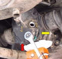 There are a series of 15 and 17mm bolts holding the cover to the housing, use a socket and remove these (red arrow); you may have to lower the differential a small amount to get access to the top bolt.