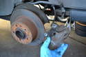 Remove the brake caliper and rotor and hang the caliper out of the way; NEVER let the caliper hang by the brake line.