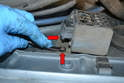 Use an 8mm wrench and remove the two screws mounting it to the inside of the fender (red arrows).