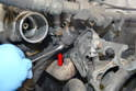 Use a 13mm wrench and disconnect the hose to EGR valve clamp (red arrow).