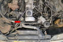 Next use a flathead screwdriver and remove the clamp and hose from the top hose to thermostat housing (red arrow).