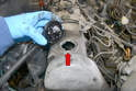 Move to the top of the motor and remove the oil filler cap from the valve cover (red arrow).