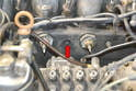 Use a 12mm wrench and gently screw the reamer in and out of the glow plug hole (red arrow) taking it out on each pass to clean the carbon off the reamer.