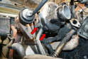 Remove the two 13mm bolts holding the oil return or down tube to the compressor (red arrows).